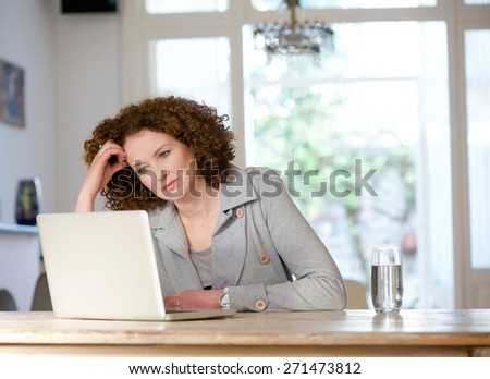 Portrait of an attractive older woman looking at laptop at home - stock photo