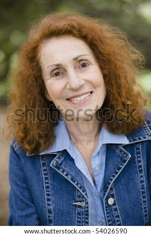 Portrait of an Attractive Redhead Senior Woman in a Denim Jacket - stock photo