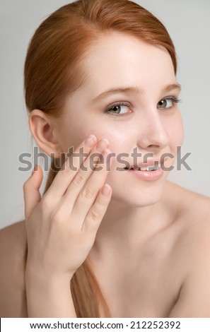 Portrait of an attractive redhead teen model with clean fresh skin on light background  - stock photo