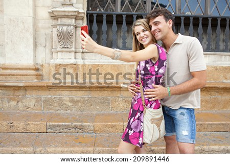 Portrait of an attractive romantic young couple relaxing taking a selfie picture of themselves with a smartphone while visiting a destination city on holiday, together outdoors. Technology lifestyle. - stock photo