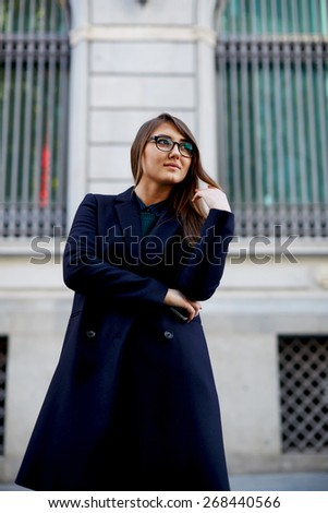 Portrait of an attractive smiling woman standing  in an urban setting looking away - stock photo