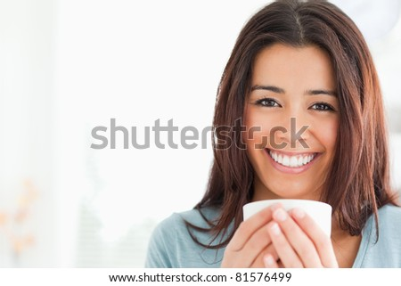 Portrait of an attractive woman enjoying a cup of coffee in the kitchen - stock photo