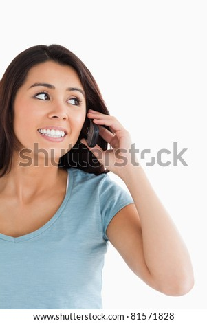 Portrait of an attractive woman on the phone posing against a white background