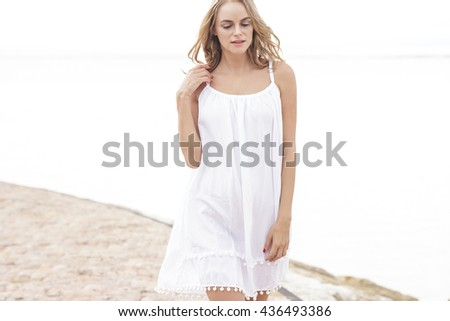 portrait of an attractive woman walking on the beach - stock photo