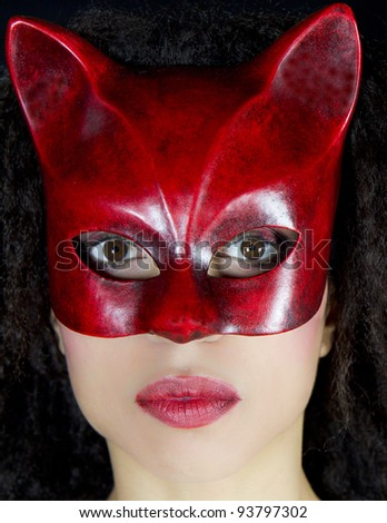 Portrait of an attractive woman wearing a red venetian mask. She is looking at camera. She is posing in front of a black background. - stock photo