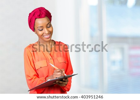 Portrait of an attractive young american african business woman with clipboard - stock photo