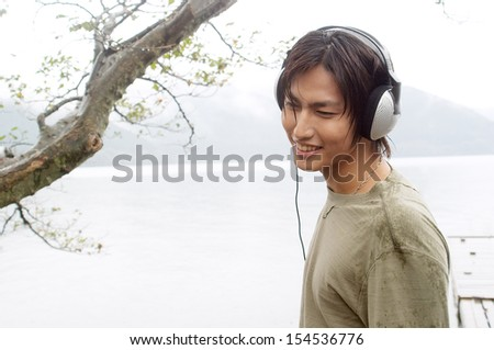 Portrait of an attractive young asian man listening to music with his headphones while visiting and contemplating a beautiful lake landscape during a autumn rainy day, outdoors. - stock photo