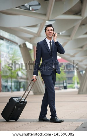 Portrait of an attractive young business man traveling with bag and talking on phone in the city - stock photo