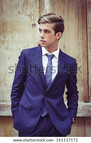 Portrait of an attractive young businessman in urban background wearing blue suit a necktie. Blonde hair - stock photo