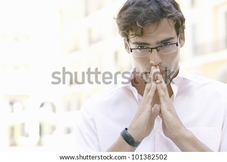 Portrait of an attractive young businessman with an uncertain expression in the city. - stock photo