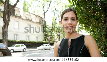 Portrait of an attractive young businesswoman smiling in a leafy street in the city with classic architecture. - stock photo