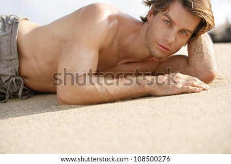 Portrait of an attractive young man laying down on the white sand of a tropical beach. - stock photo