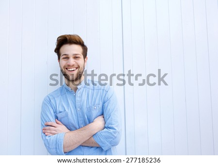 Portrait of an attractive young man smiling with arms crossed  - stock photo