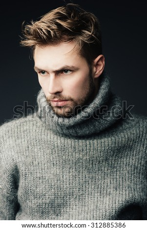 Portrait of an attractive young man with a beard in the studio - stock photo