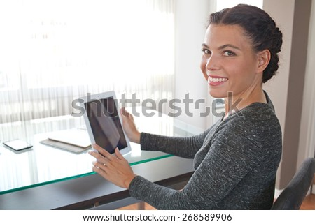 Portrait of an attractive young professional business woman sitting at her work desk working and using a tablet, office interior. Businesswoman in office using technology against a window, indoors. - stock photo