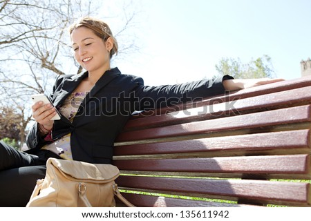 Portrait of an attractive young professional woman using a smartphone while sitting on a wooden bench in a park, smiling. - stock photo