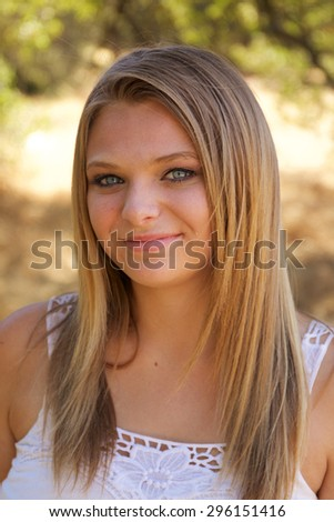 Portrait of an attractive young teenage girl smiling in the park with blonde hair on a sunny day - stock photo