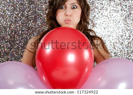 Portrait of an attractive young woman against a silver glitter background, holding three balloons in red and pink and pulling faces.