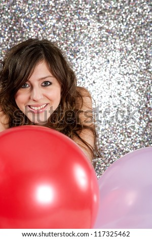 Portrait of an attractive young woman against a silver glitter background, holding two balloons in red and pink colors, smiling.