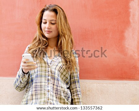 Portrait of an attractive young woman leaning on a colorful old city wall using a high tech smartphone and wearing a checked shirt, smiling. - stock photo