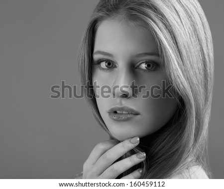 Portrait of an attractive young woman on a gray background