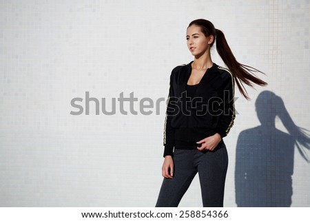 Portrait of an attractive young woman ready for a workout standing with dynamic flying hair on white background at beautiful sunny day - stock photo