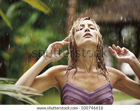 Portrait of an attractive young woman under the tropical rain, tilting her head back and feeling the rain falling on her face. - stock photo