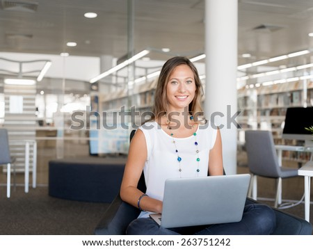 Portrait of an attractive young woman using her laptop - stock photo