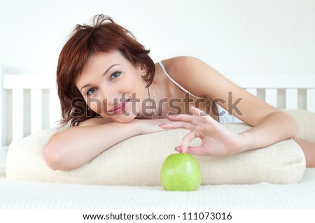 Portrait of an attractive young woman with an green apple at bed - stock photo