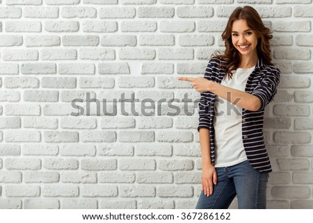 Portrait of an attractive young woman with dark wavy hair, looking into the camera, with white teeth, fingers gestures upwards, on a background of a brick wall - stock photo