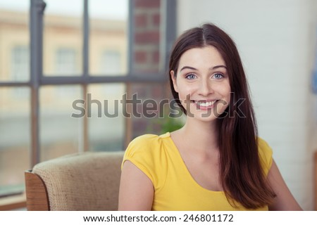 Portrait of an attractive young woman with long straight brown hair worn over one shoulder sitting looking at the camera with a lively interested smile - stock photo