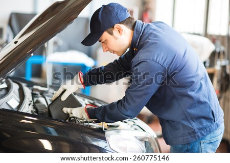 Portrait of an auto mechanic putting oil in a car engine - stock photo