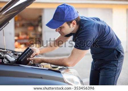 Portrait of an auto mechanic putting oil in a car engine