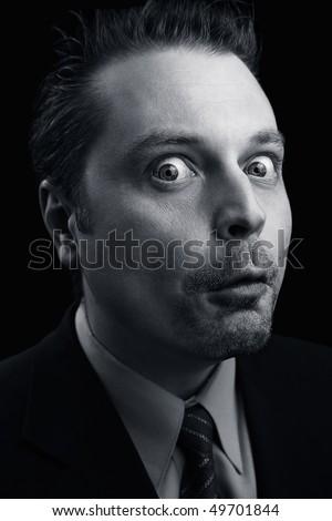 Portrait of  an eccentric man on a dark background - stock photo