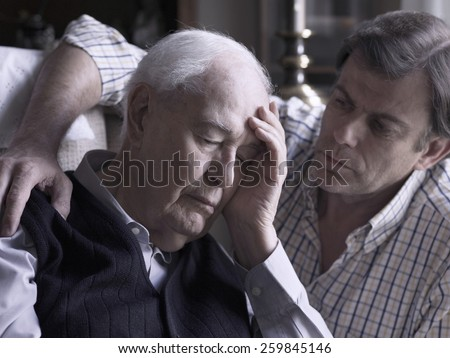 Portrait of an elderly man, comforted by his son - stock photo