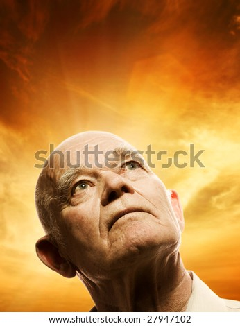 Portrait of an elderly man looking up - stock photo