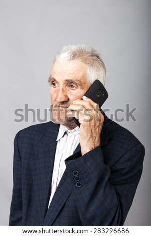Portrait of an elderly man using mobil phone against gray background - stock photo