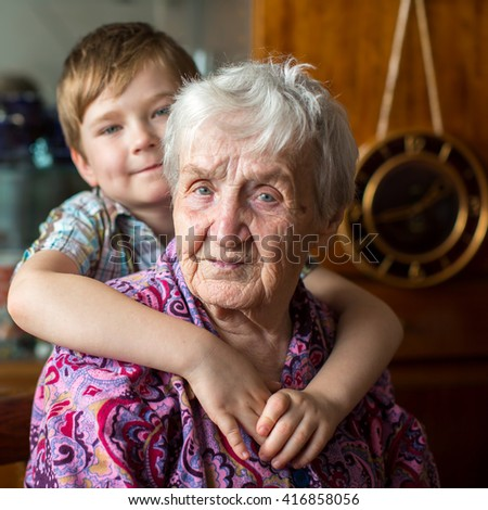 Portrait of an elderly woman, grandson at blurring in the background. - stock photo