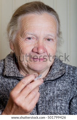 Portrait of an elderly woman on a light background.
