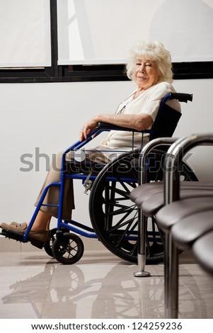 Portrait of an elderly woman on wheelchair in hospital lobby - stock photo