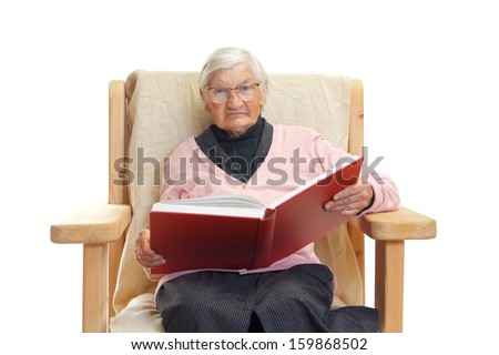 Portrait of an elderly woman reading a book - stock photo