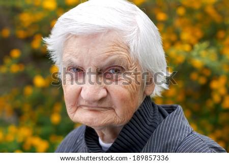 Portrait of an elderly woman walking in the garden - stock photo