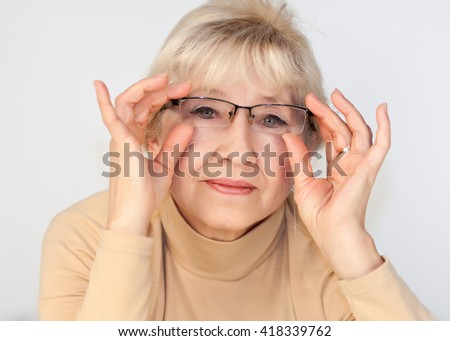 Portrait of an elderly woman with glasses - stock photo