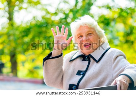 portrait of an elderly woman with gray hair in the park - stock photo