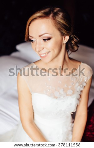 Portrait of an elegant bride sitting indoors - stock photo