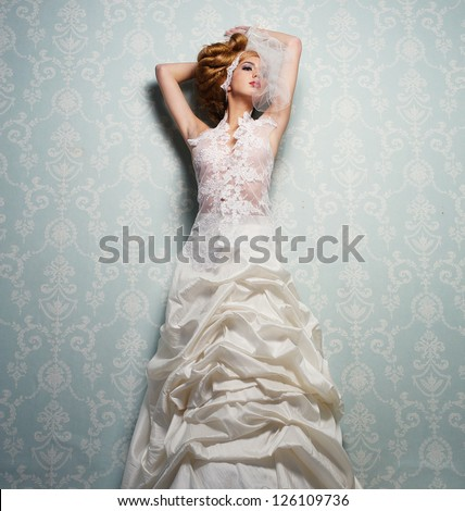 Portrait of an elegant bride standing against a wall - stock photo