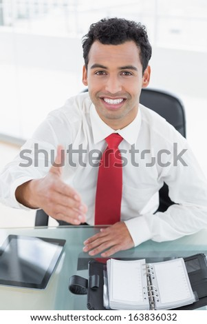 Portrait of an elegant businessman offering a handshake at office desk - stock photo