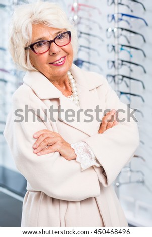 Portrait of an elegant elderly woman at the optician's, wearing trendy glasses