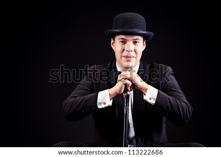 Portrait of an elegant man in black suit and black pot hat holding walking stick. Black background. - stock photo