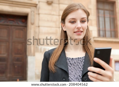Portrait of an elegant professional businesswoman standing by a grand stone building in the city, smiling and using a smartphone. Business people with technology in an office district, outdoors. - stock photo